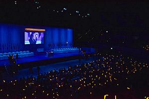 「稲村の火」に敬意を示し、オレンジ色のライトとトーチを掲げる高校生ら
