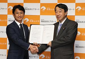 協定書を手に瀧学長㊨と岡田社長