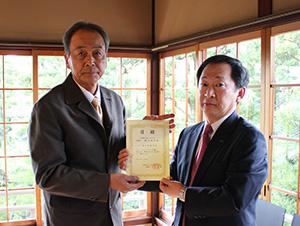 助成金の目録を手にする橋爪会長㊧と花田常務理事