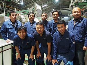 研修中の工場で実習生6人と吉田社長㊨、岡山部長㊧