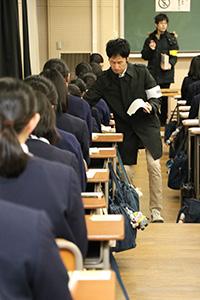 解答用紙を配布する試験官(和歌山大学で)
