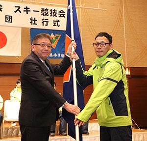 宮下教育長㊧から団旗を受け取る岸裏選手