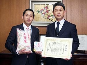 感謝状と金芽米を手に谷田社長㊧と阪本副社長