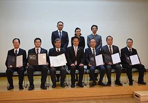 認定証を手に事業者と尾花市長(前列中央)と審査委員ら