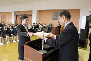上野校長㊨から卒業証書を受け取る卒業生