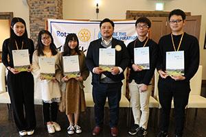 卒業アルバムを手に留学生と石塚会長(右から3人目)