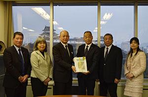 文集を渡す黒井課長(中央左)と原教育長(中央右)