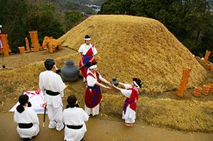 古代人に扮し、復元された古墳と埴輪の前で葬送儀礼を行う参加者