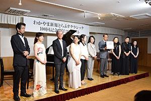 出演した8人の演奏家の皆さんと梅田社長(左から6人目)、高橋委員長(同7人目)