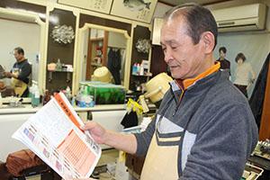 店で大会ガイドブックを眺める中本さん