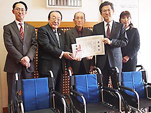寄贈された車椅子と西岡会長(中央)、石橋社長(同右)ら