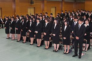 緊張した表情で入学式に望む新入生