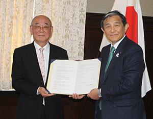 協定書を手にする田中学長㊧と仁坂知事