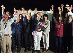 支援者と喜びの万歳三唱をする桐山さん(中央)