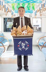 鯛コロッケとバーガーを手に義本総支配人(休暇村紀州加太提供)