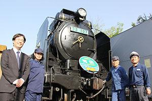 バイオ燃料で走るデゴイチと次田さん㊧や機関士、整備士の皆さん