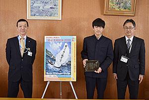 最優秀賞のポスターと(左から)森事務局長、菅沼君、勝本校長