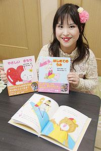 2冊の絵本を手に笑顔の髙田さん