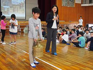 承子さま(中央)を講師に水がめを運ぶ体験をする児童