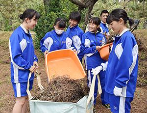掃除した葉を集める生徒たち