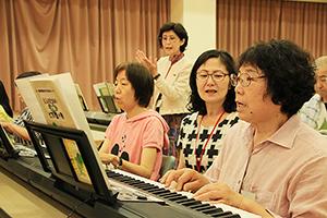両手でピアノ演奏に取り組む受講者