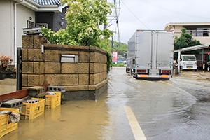 冠水した道路を通行するトラック(7日午前11時27分、和歌山市平尾)
