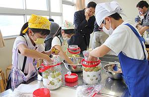 ウメを使ってジュースを作る児童たち