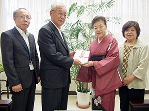 石田会長(左から3人目)が中芝市長に募金の目録を手渡した