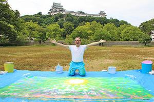 和歌山城を背景に、完成した作品と大西さん