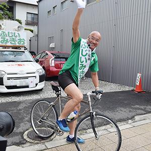 自転車で出発する藤井候補