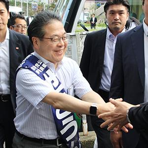 支援者と笑顔で握手をする世耕候補