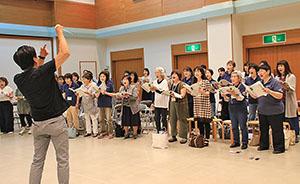 藤岡さん㊧の指揮で練習に臨む団員ら