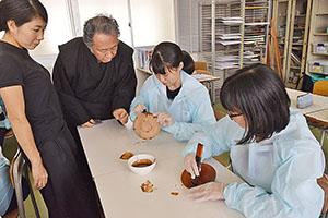 塗り方を指導する曙山さん(左から2人目)