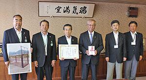 中芝市長(右から3人目)に目録を贈呈した田代表理事組合長(左から3人目)
