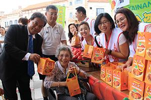 笑顔でマンゴーを受け取り、台南市議に囲まれる来場者