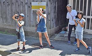 路地を撮影する児童たち