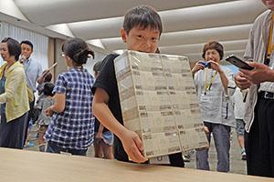 1億円の束を抱える児童
