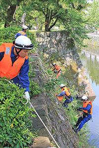 ロープで石垣に降下し、清掃する消防隊員ら