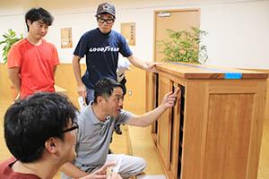 一級技能士の手作り家具を眺める来場者