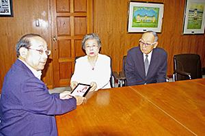 髙瀨事務局長㊧に寄付金を手渡す永岡部長㊥