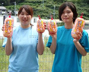 新発売の「みかんパン」を手に(右から)宮﨑さん、坂本さん