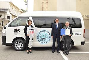 車両の前で(左から)栩原さん、勝股副支社長、栩原理事長