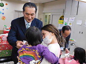 子どもに菓子をプレゼントする高橋さん