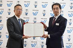 協定書を手に檜垣本部長㊧と関戸会長