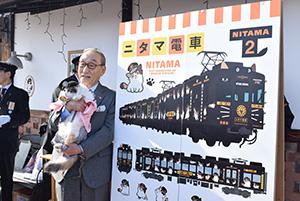 発表されたニタマ電車デザインとニタマを抱く小嶋社長
