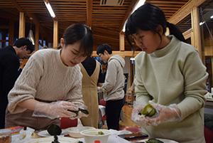 高菜でご飯を包む学生ら
