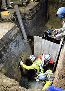 修繕した水道管の事後処理をする作業員ら(20日午前2時38分)