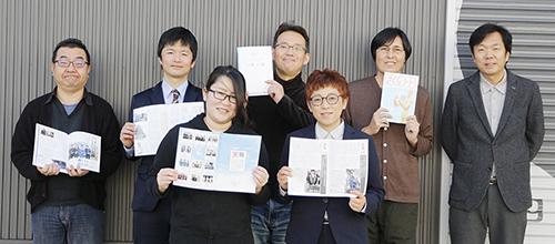 『さくらノート』を手に松下代表(後列右)と編集人の宇治田さん(後列左から2人目)と編集チームの皆さん(㈱ウイング提供)
