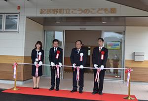 玄関前でテープカットを行う寺本町長(左から3人目)ら