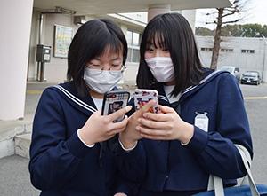 スマートフォンで合格発表を見る受験生